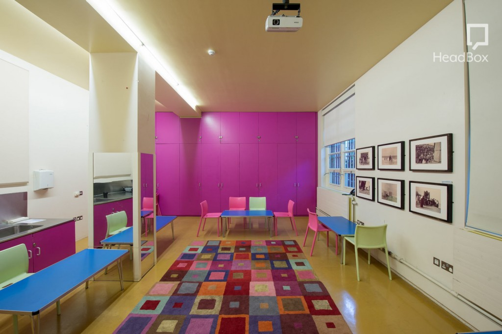 Large meeting room with pink cupboards and kitchen units. Three blue tables line the walls with small pink and green chairs tucked underneath. There is a colourful carpet in the centre of the room.