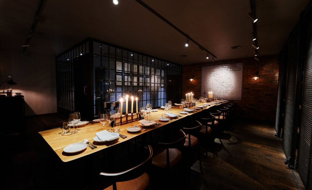 a dimly lit private dining room with a long wooden table in the centre of the room. The table is set with candles, plates and cutlery and there is a large window on the back wall which shows that it is dark outside.