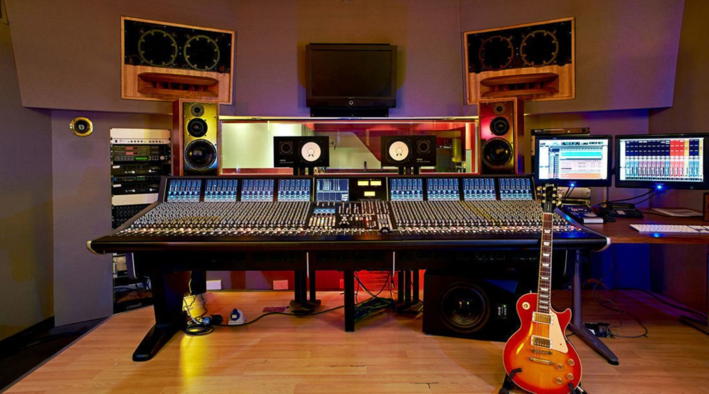 a large mixing deck, multiple speakers, screens and a red electric guitar in front of the deck