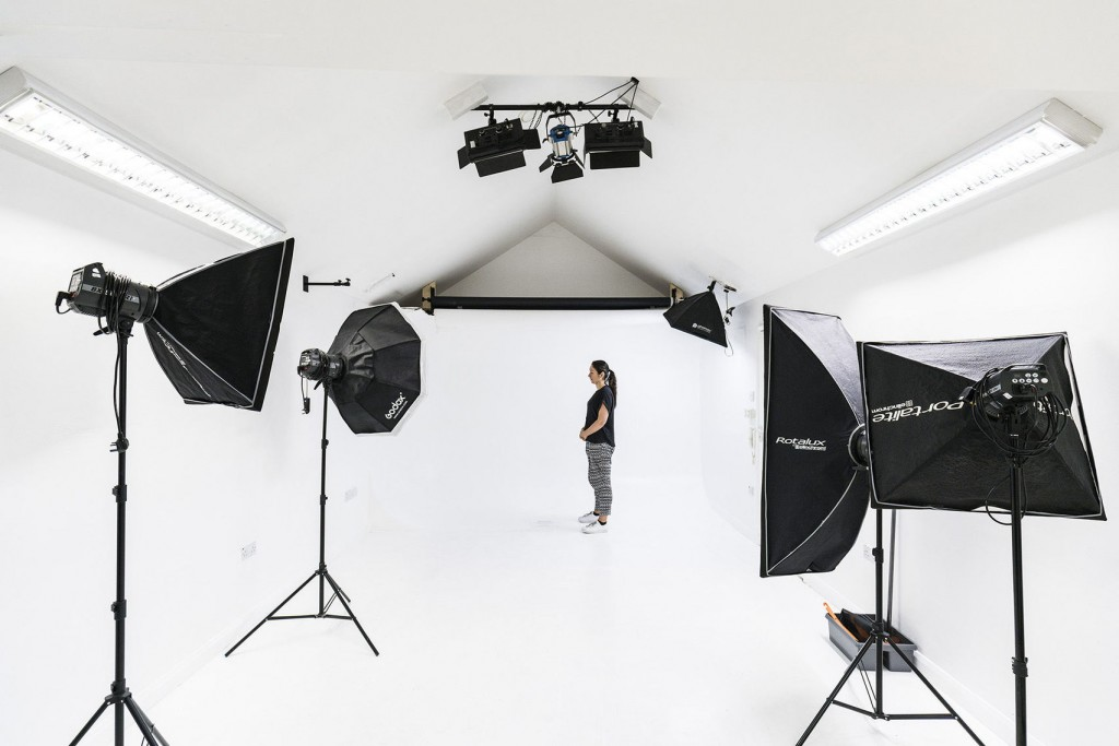 a large white studio with black camera equipment pointing towards a figure standing in the background