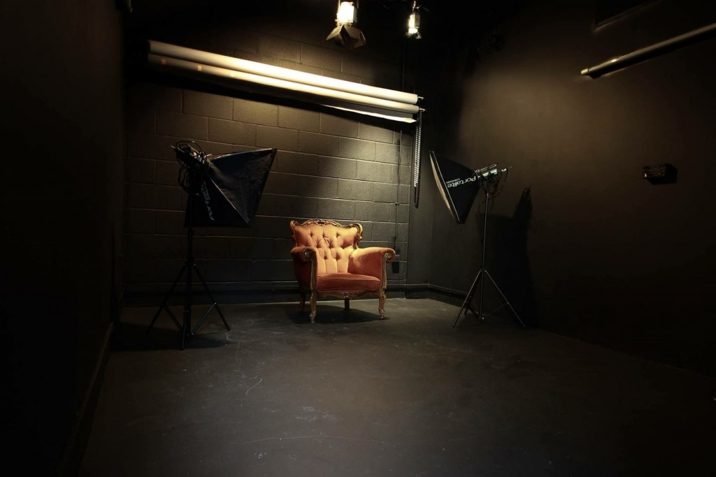 a black room with two large camera lights pointing towards an orange armchair.