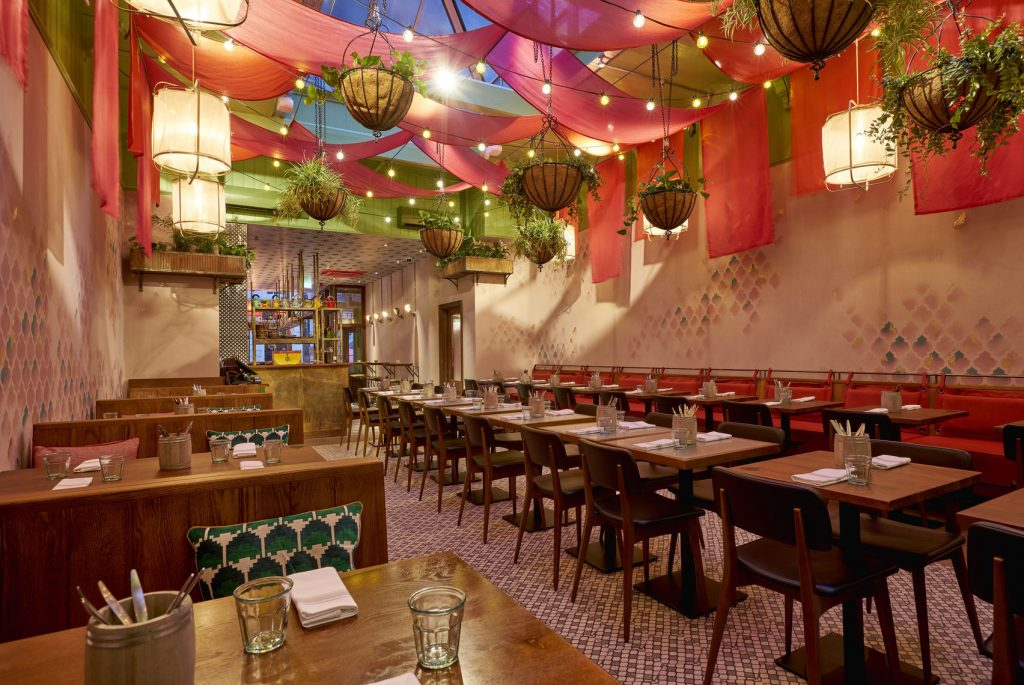 a brightly decorated restaurant with bright coloured material and fairy lights hanging from the ceiling as well as hanging baskets. There are various tables and chairs set up around the room.