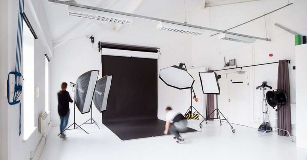 A white room with a large black backdrop screen on the back wall with lots of large camera equipment pointing towards it.