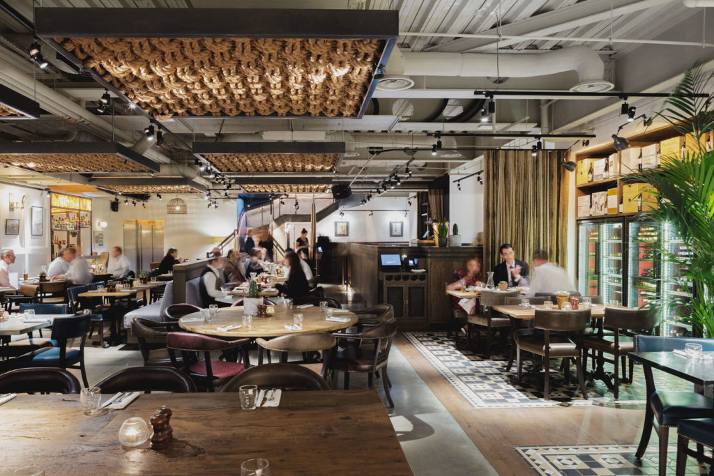 A large restaurant in Moorgate that has a range of tables that people are sat at- gold art decor ceiling and green plants dotted around