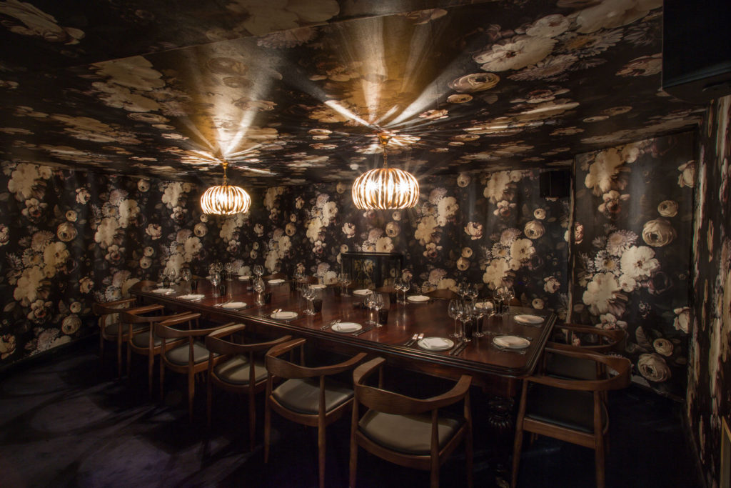 A private dining room in London that has flower wallpaper and a long wooden table in the middle