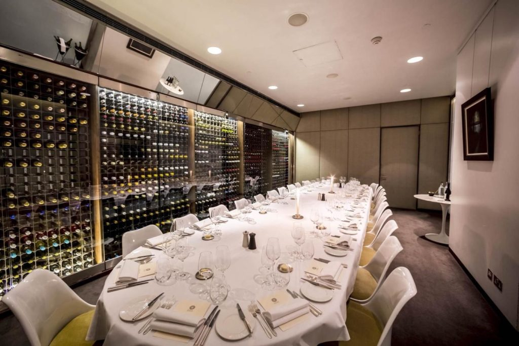 A private dining room with one long table in the middle and the back wall is a huge wine rack