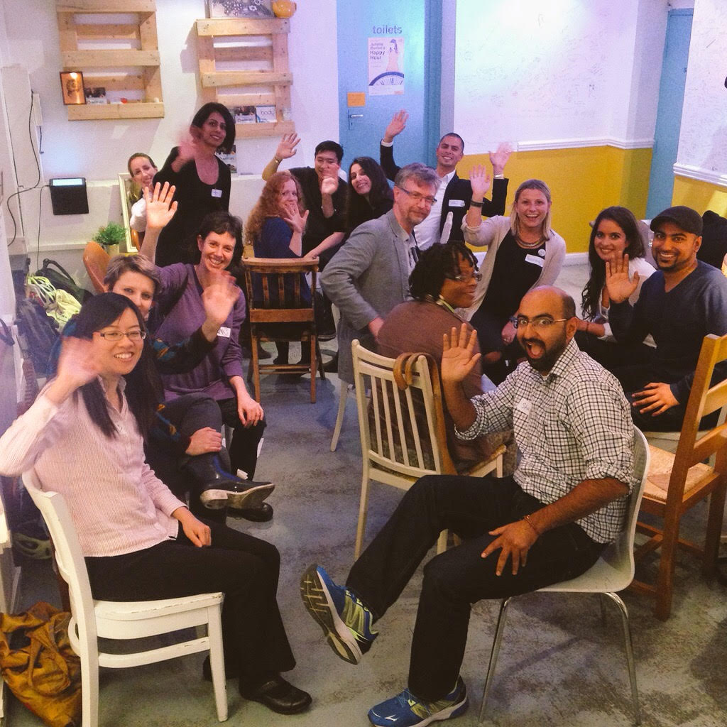 a quirky cafe room with a large group of people all smiling and waving at the camera