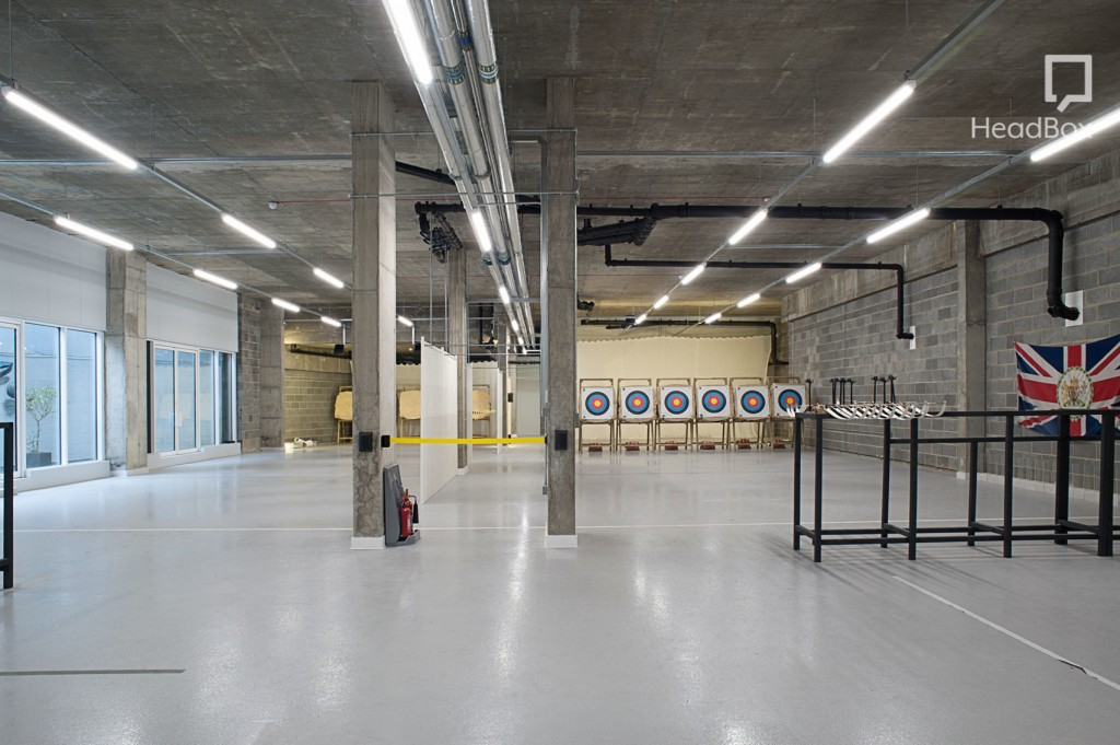 Archery Fit, Archery club London. Large industrial room with concrete ceiling, pillars and grey brick walls. six archery targets are lined up along the back wall of the Space.