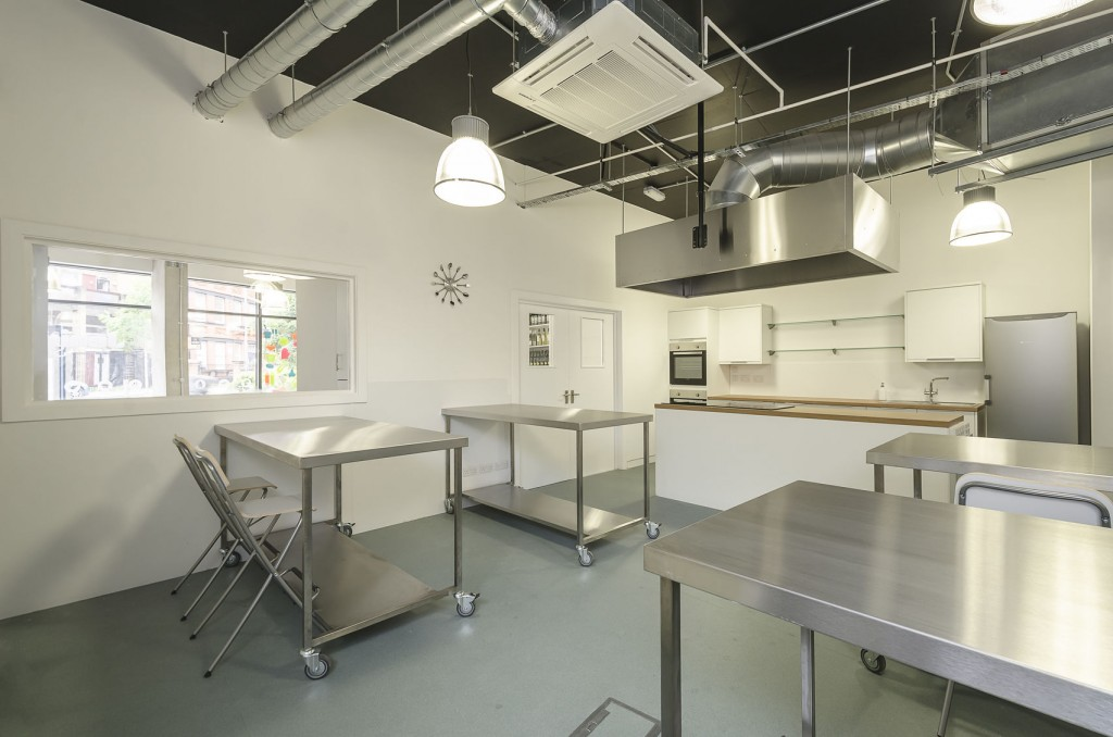 Jenius Social, a kitchen Space with four stainless steel work trollies, a low hanging extractor fan and lights and a large white kitchen counter with a wooden top facing the work tables. A fridge and oven sit behind the counter.