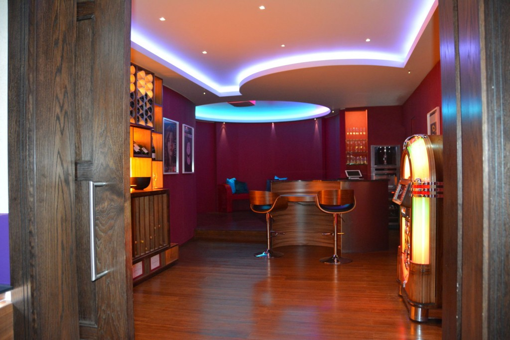 Games Room, Cornflake. Trendy games room with a small bar, with two wooden bar stools. A circular seating area sits behind the bar, and there is a retro duke box against the right wall. Florescent mood lighting shines from the ceiling and portraits hang on the walls.