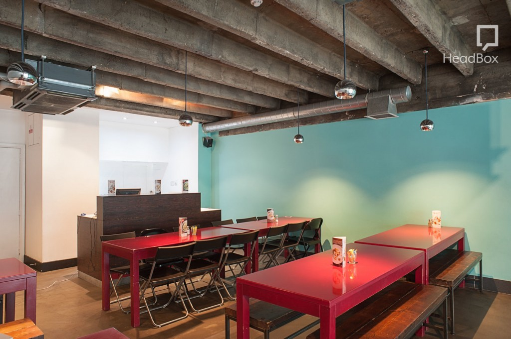 Hummus Bros restaurant. Large room with one turquoise wall, exposed ceiling, wooden service counter, and two long bright red tables.