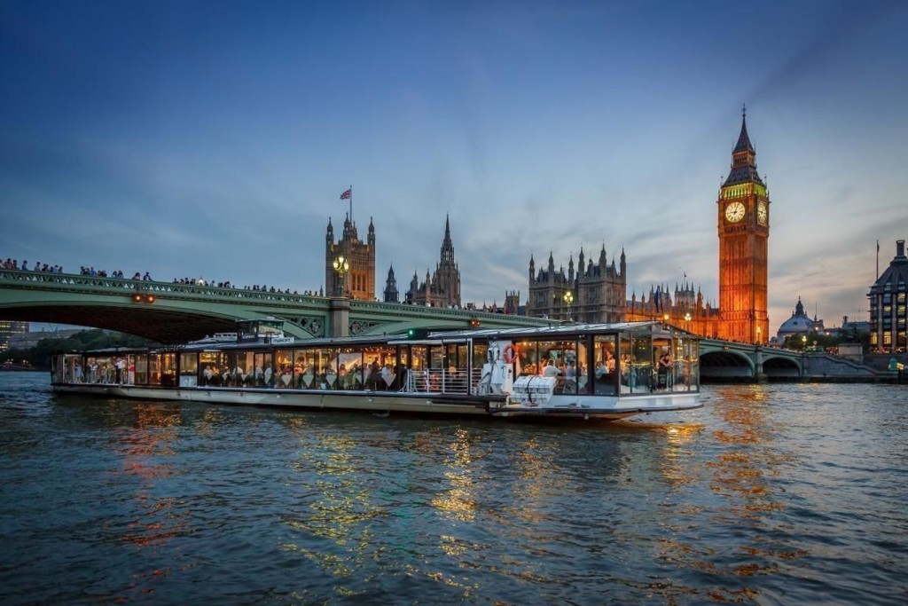 Bateaux London for hire, a long boat on the river thames in front of big ben at dusk.