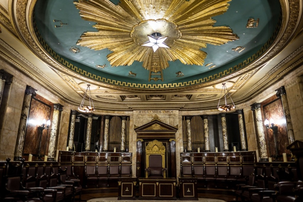 Masonic Temple at The Andaz London, grand looking room with gold and blue zodiac symbol piece on the ceiling. The Walls are made of marble and there are rich dark brown pews around the edges of the room. A large thrown-like chair with a gold and mahogany frame sits in the centre of the far wall
