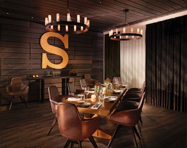 A private dining room with a large S on the wall
