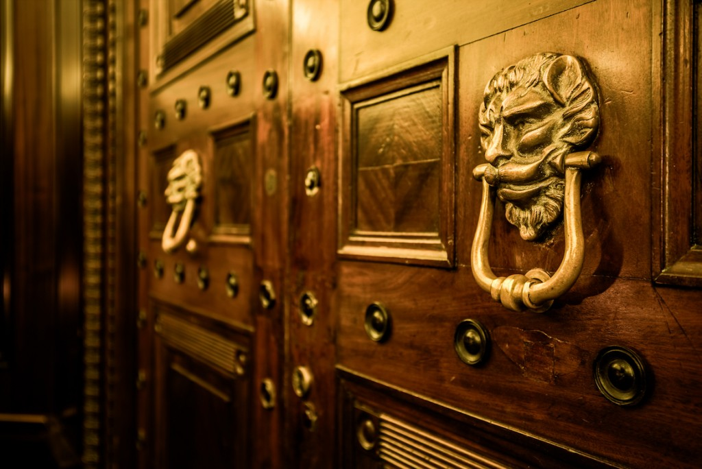 Gold door knockers made of stylised bearded faces on a bronze studded mahogany set of doors