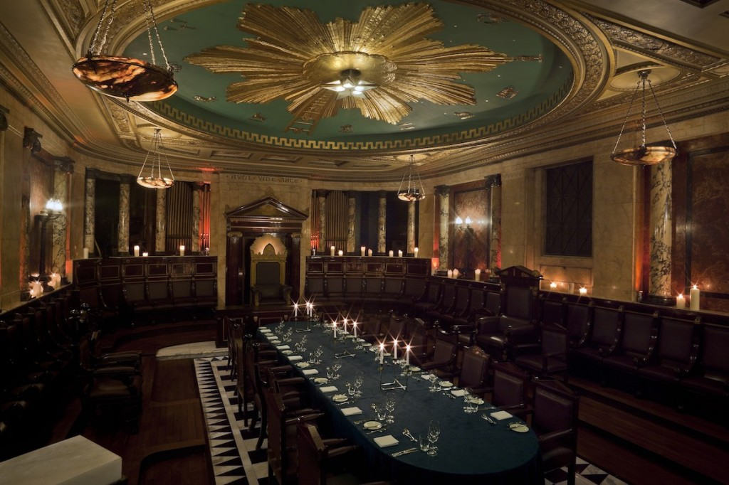Large masonic temple with wooden pews around the edge of the room, a long dining table in the centre and a large circular gold and blue zodiac detailing on the ceiling