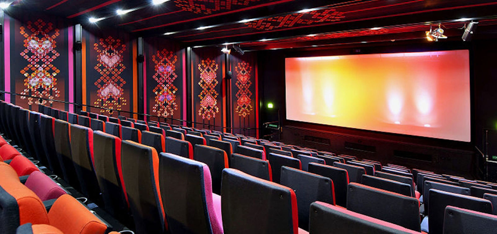 A cinema screen with red patterns on the walls