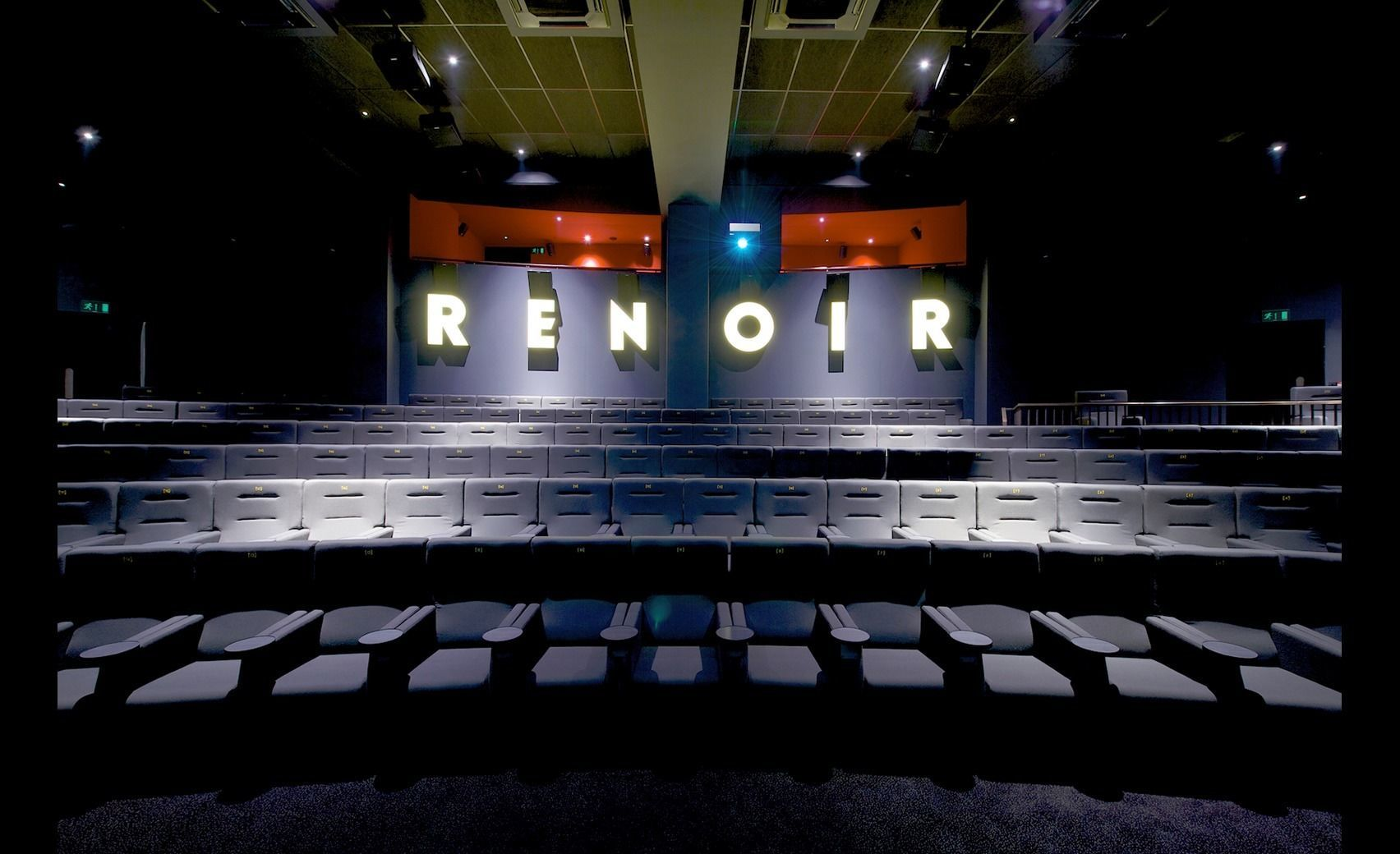 A cinema room with the words RENOIR written on the back wall