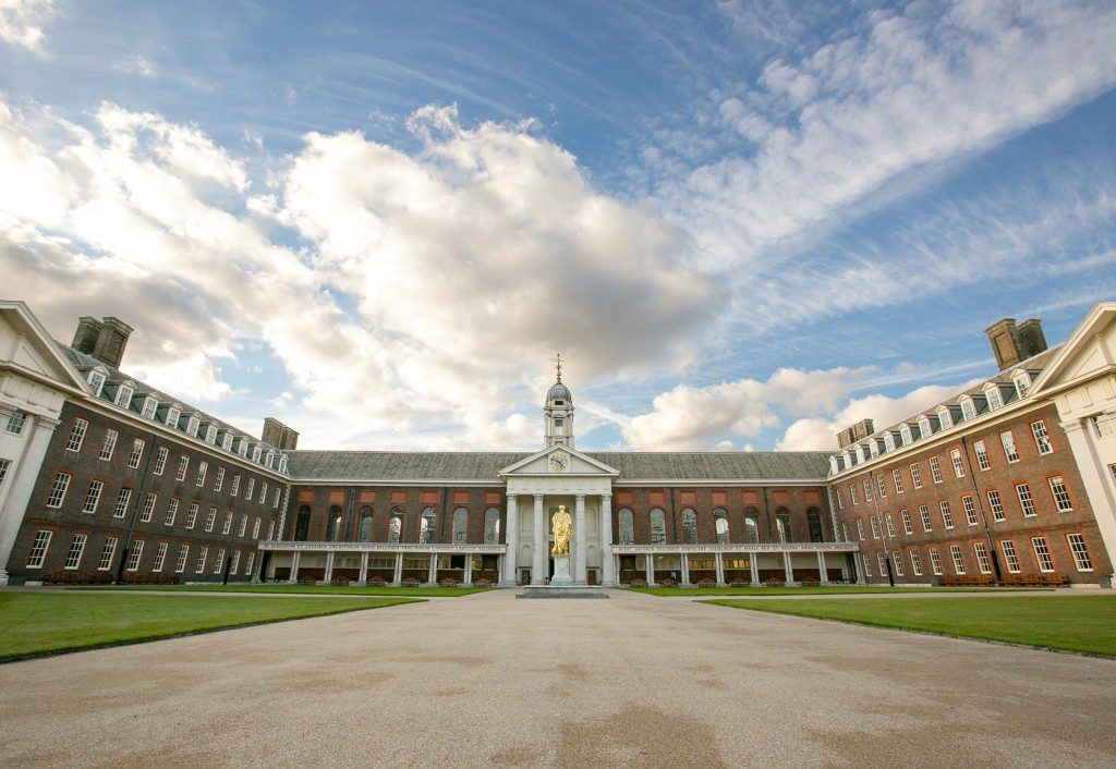 Photo of the Royal Hospital Chelsea from the quad. A grand looking building with a gold statue of a man on a plinth stands at the front centre of the building.