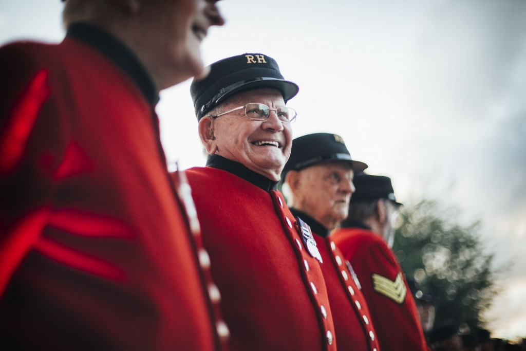 Four elderly male army veterans stand in a line wearing bright red uniforms and black hats. One of the men is wearing glasses and is grinning at something out of shot.