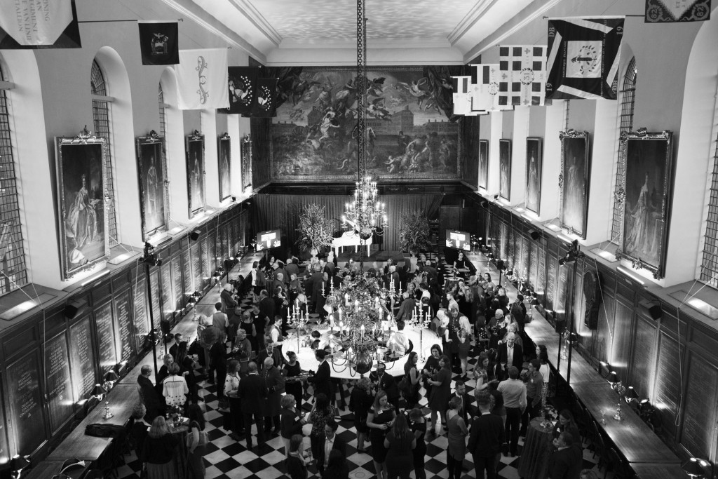 A black and white photo of a grand hall. Impressive chandeliers hang from the ceiling, extravagant oil paintings are mounted in large frames on the walls. A large crowd of people are milling around a circular bar in the centre of the room. A large renaissance painted mural covers the upper half of the furthest wall.