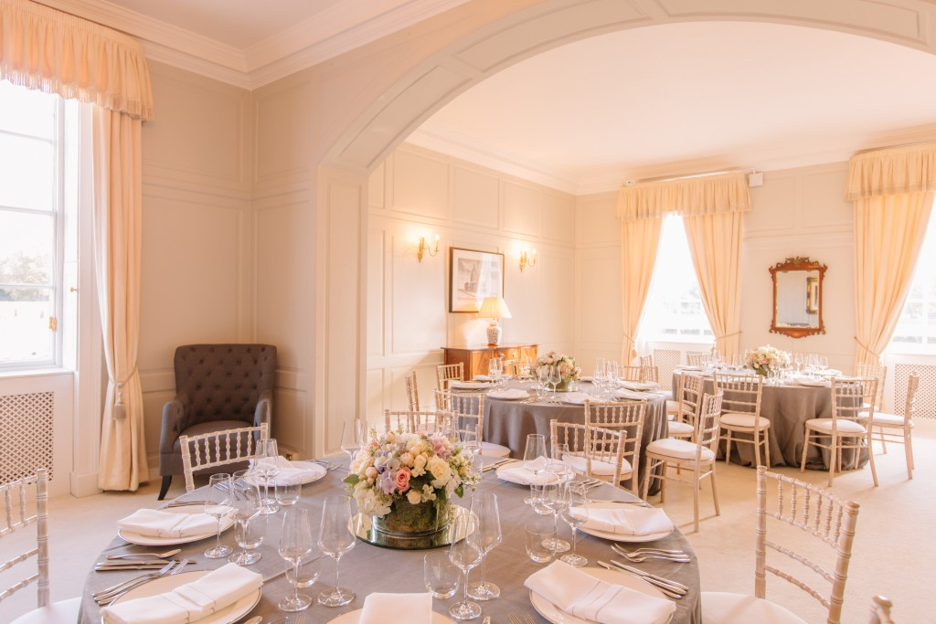 Three circular tables with pale grey tablecloths and laid for a smart meal are arranged in a Bright room with cream walls, carpet and curtains. There are small flower centrepieces on each table.