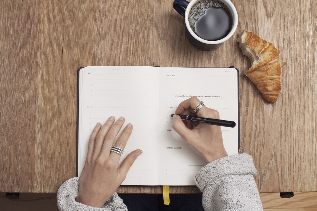 A person writing on a notebook which has a croissant and coffee next to it