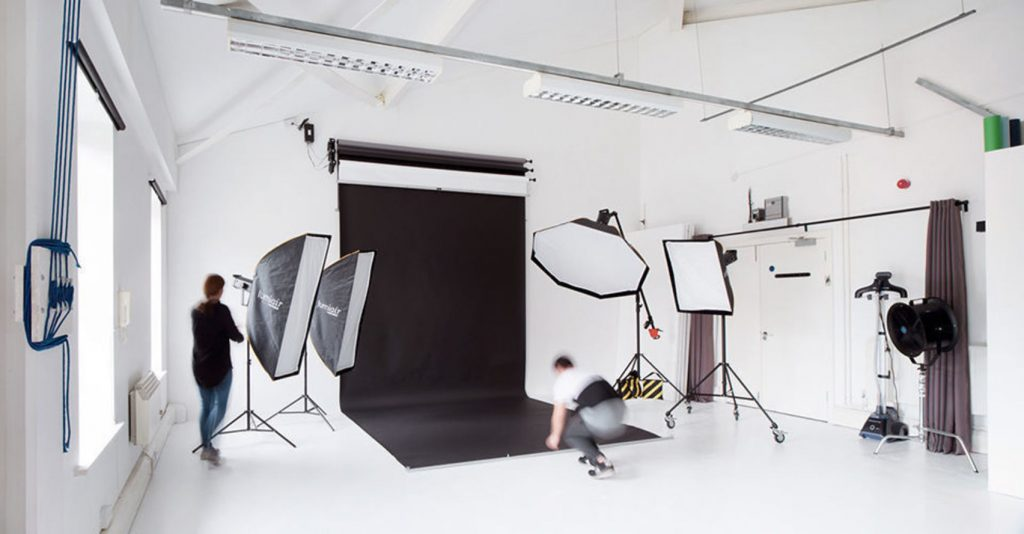 a large white room with a black screen hanging from the ceiling. There are large photography lights pointing towards this screen as well as two people rearranging other camera equipment.