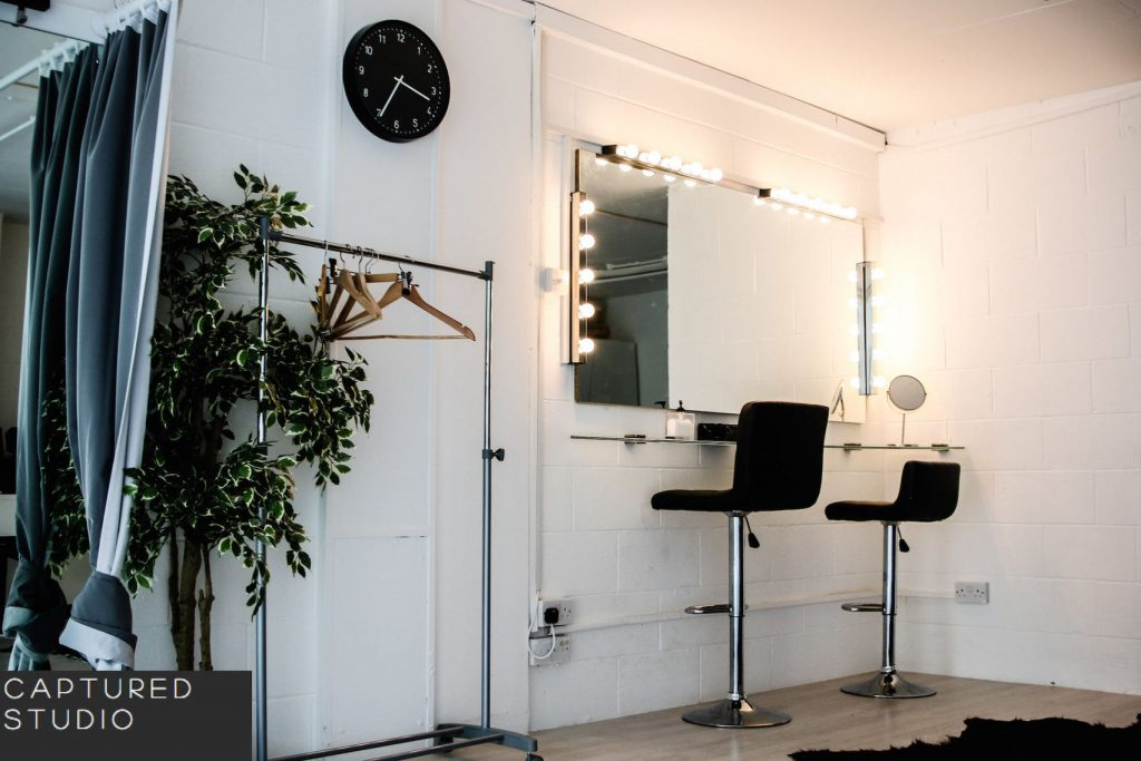 a large white room with a mirror surrounded by a frame of lightbulbs is one wall with two stools up against it ready for hair and make up sessions. There is a black clock on on the same wall and a large pant pot placed on the ground.