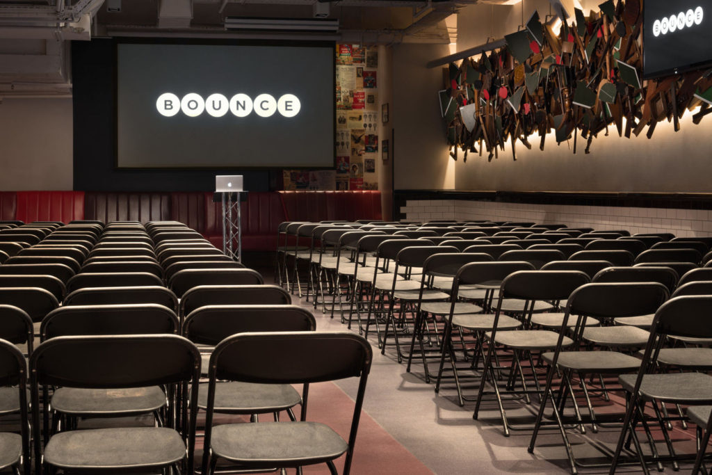 Large meeting room in Farringdon with screen and rows of chairs.