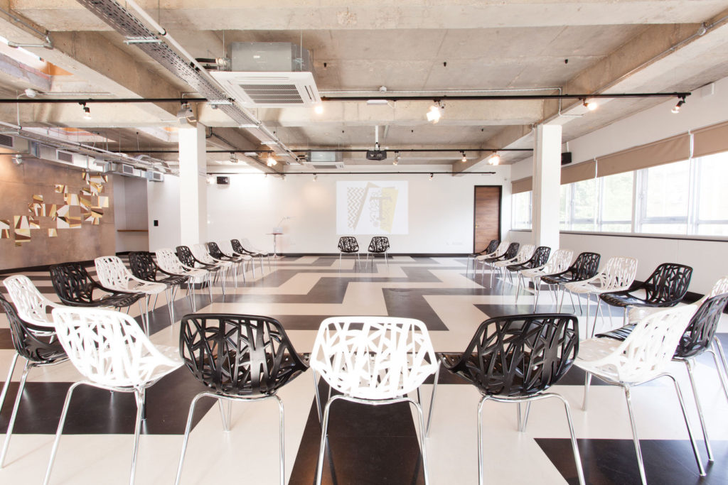 Large, open-concept space with concrete ceiling, black and white chairs and patterned flooring.