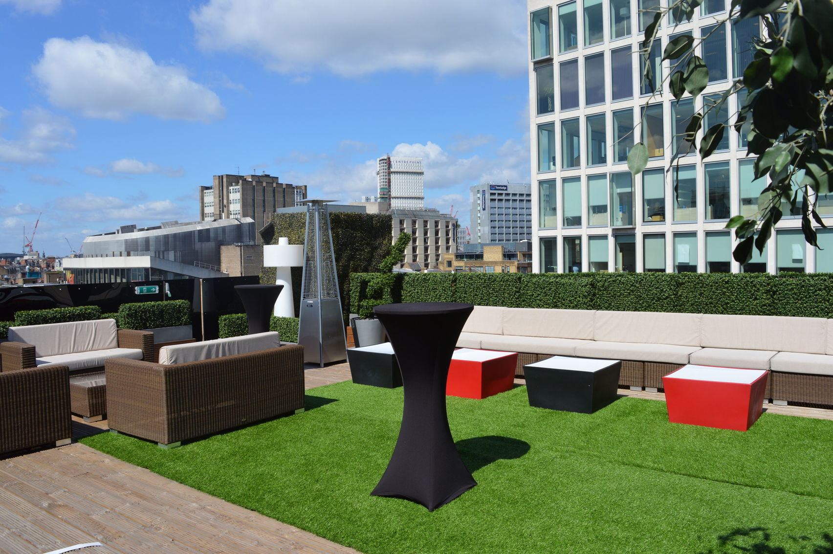 A rooftop terrace with fake grass and black and red seats