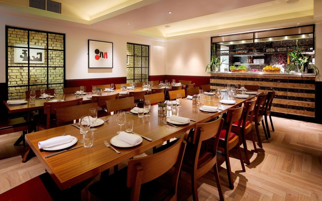 A private dining room with a wooden table and chairs surrounding it.