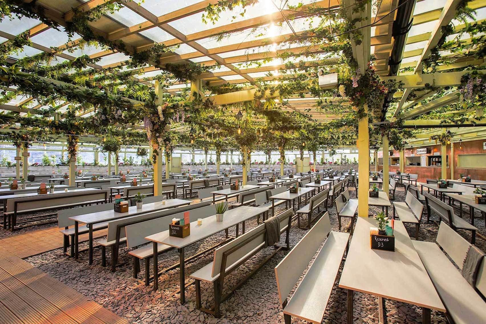 A huge rooftop bar with picnic benches and covered with a pergola