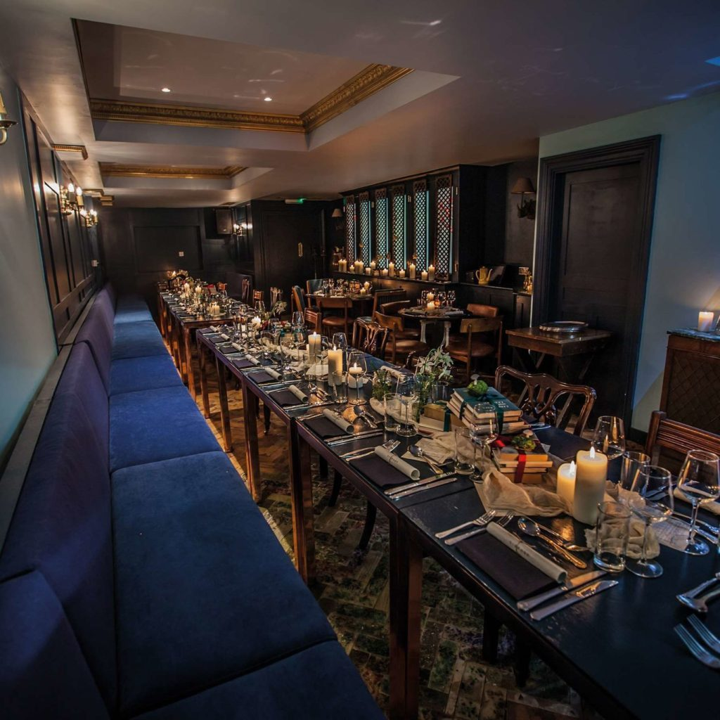 A private dining room that has a long table and a long velvet blue sofa seat on the left on side