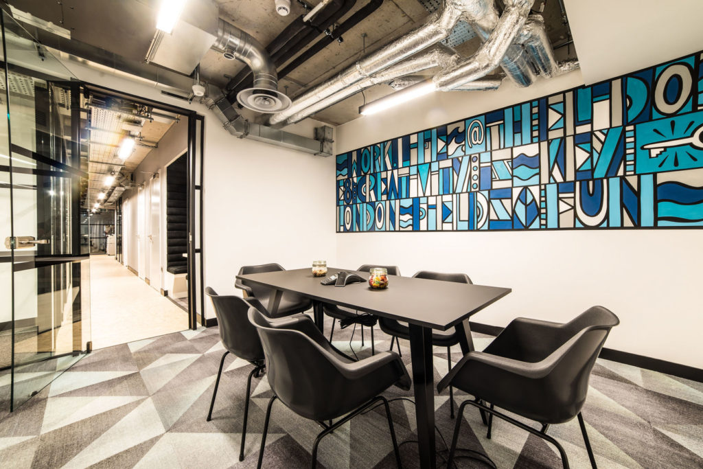 Meeting room with black tables and blue wall mural