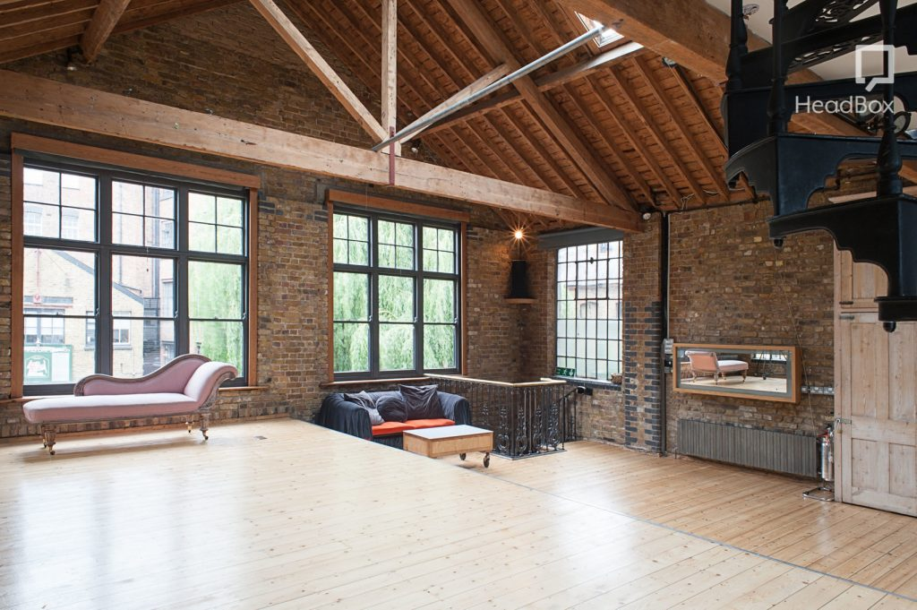 an exposed brick-work room with wooden beams running along the ceiling. There are three large cross hatched windows letting in lots of natural light.