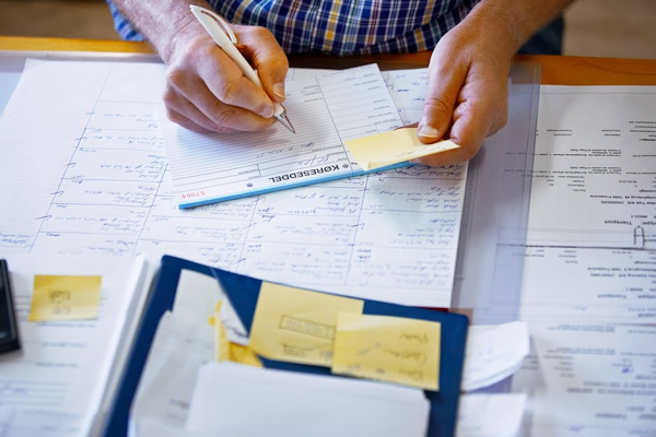 A man is writing on a notpad whilst referring to a yellow post it note. Only his hands are in shot and the rest of his desk is covered in paperwork and post its