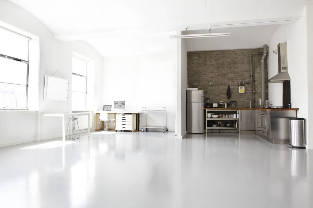 a large white room filled with natural light, has a kitchen area in the corner with an exposed brick wall that contrast the rest of the room.