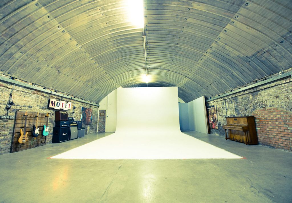 a large warehouse with a metal oval shaped roof. There is a large white screen that hangs from the wall and extends onto the floor which is set up for a photoshoot. One the side of one wall there are electric guitars hanging and a quirky signs made of scrabble pieces that reads 'MOTEL'
