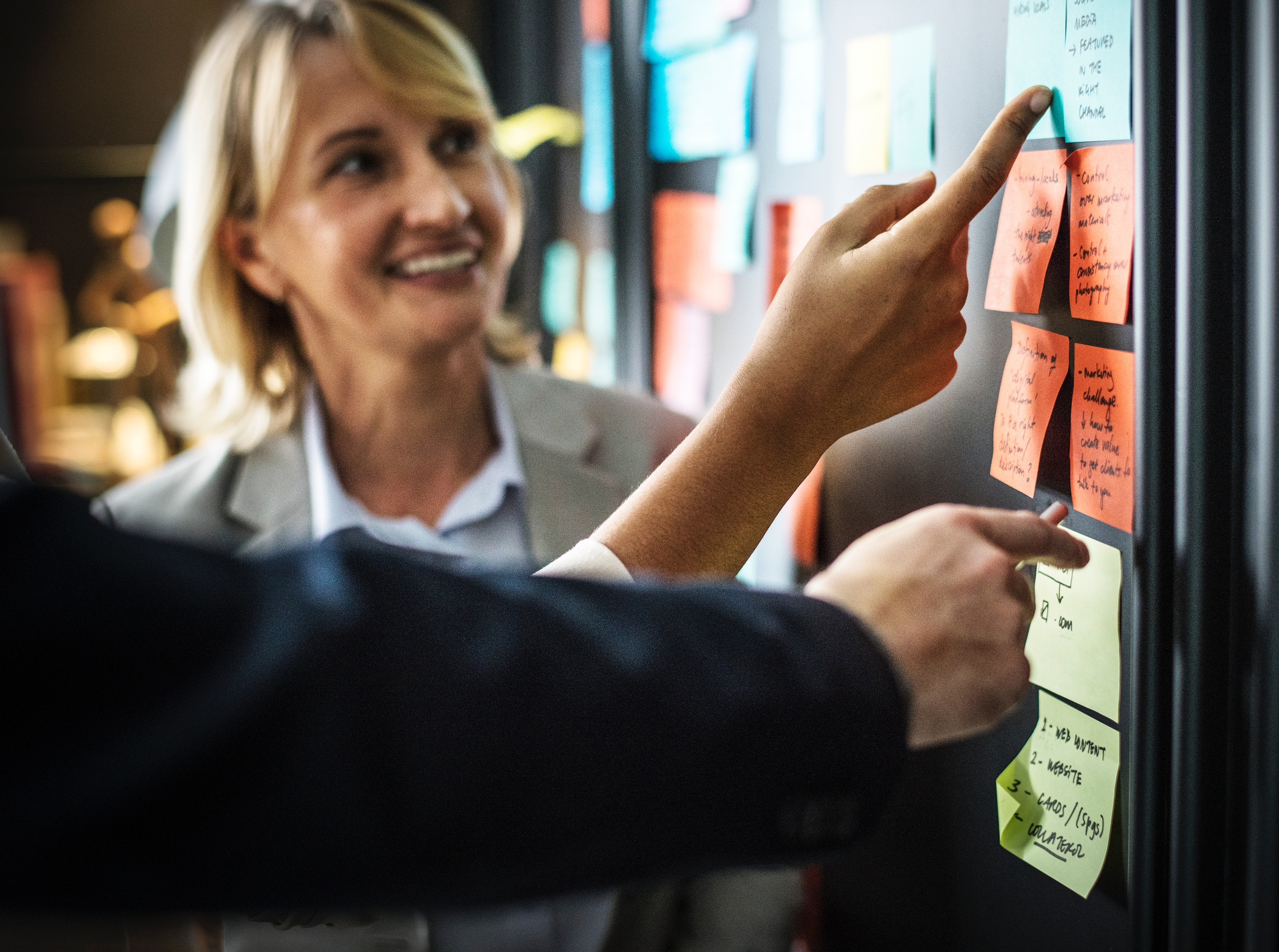 A women looking at a board with post-it notes on it