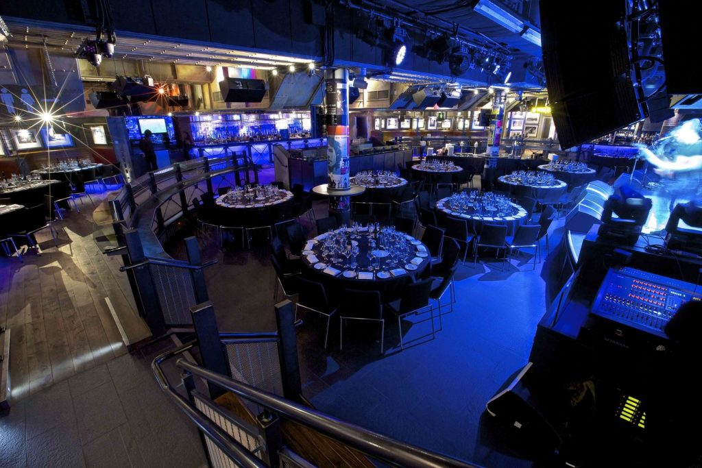 blue lit venue with round tables