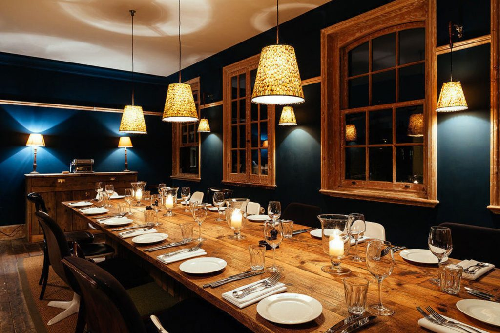 a dark navy room with a wooden table in the centre of it. There are nightshades hanging from the ceiling.