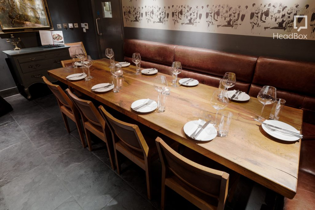 a wooden table has been set up for a meal - with sofa seating on one side and wooden chairs on the other. There are plates, cutlery and glassware set on top of the table