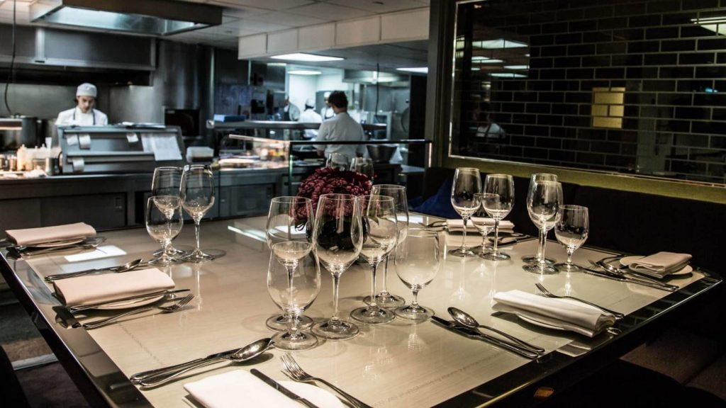 a large square private dining table laid with cutlery and glassware overlooks the kitchen of this top London restaurant