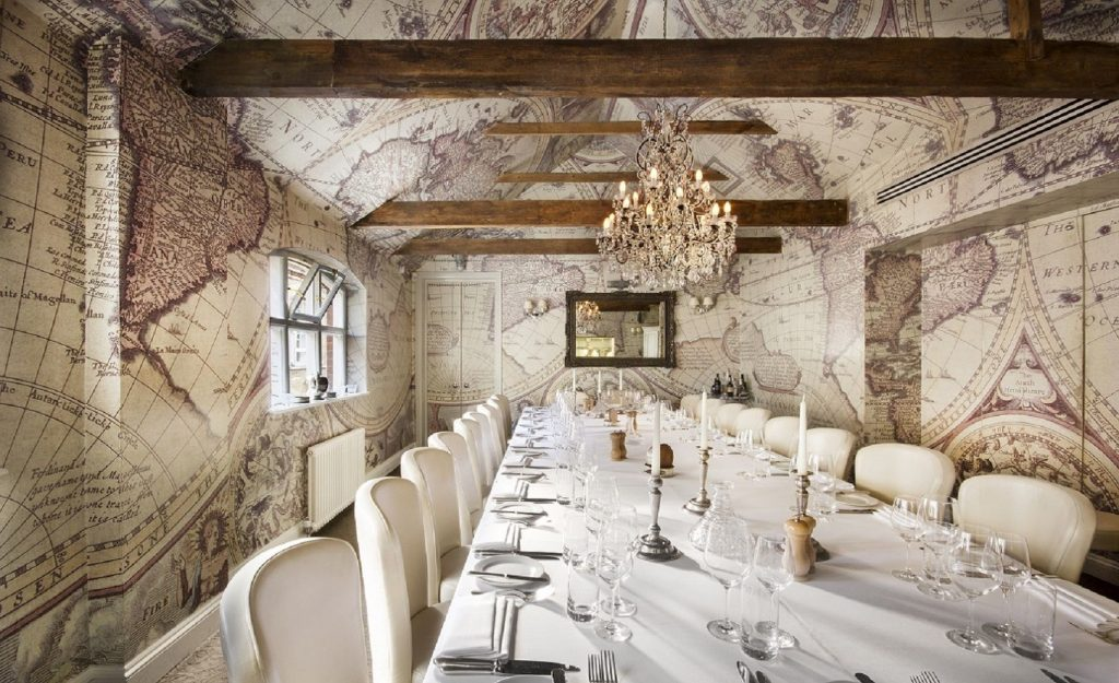 the walls of this unique private dining room are covered from floor to ceiling in maps of the globe. There is a large chandelier hanging from the ceiling which also has dark brown beams running along it. The table is set with a white table cloth, candles, side plates and glassware.