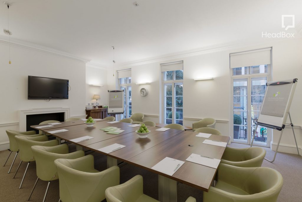 a large white room is filled with a wooden boardroom table, that has green armchairs placed around it. In one corner of the room is a white flipchart and there is a large HD screen on the wall.