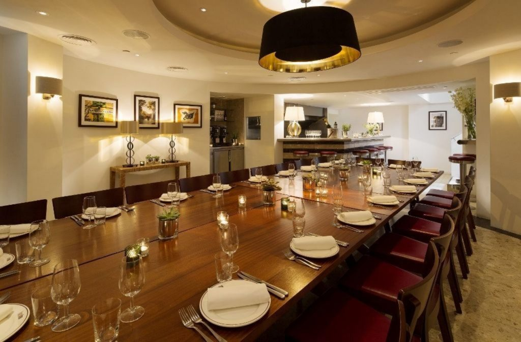 a bright and modern private dining room with a large brown wooden table in the centre the room, the table has been laid for dinner with white plates, cutlery and glassware on the table.