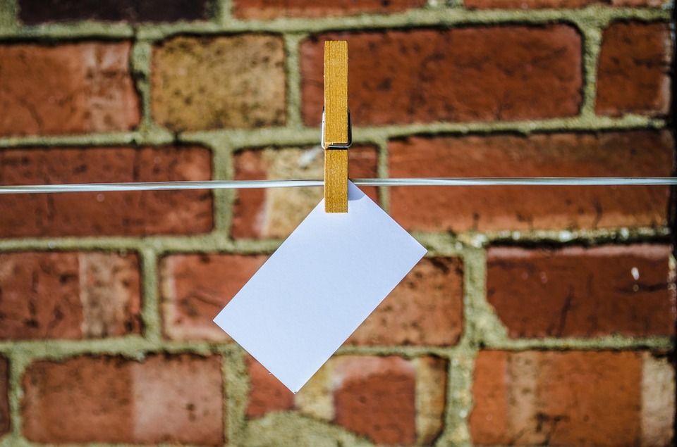 a brick wall with a washing line running in front of it with a white networking business card pegged to it.