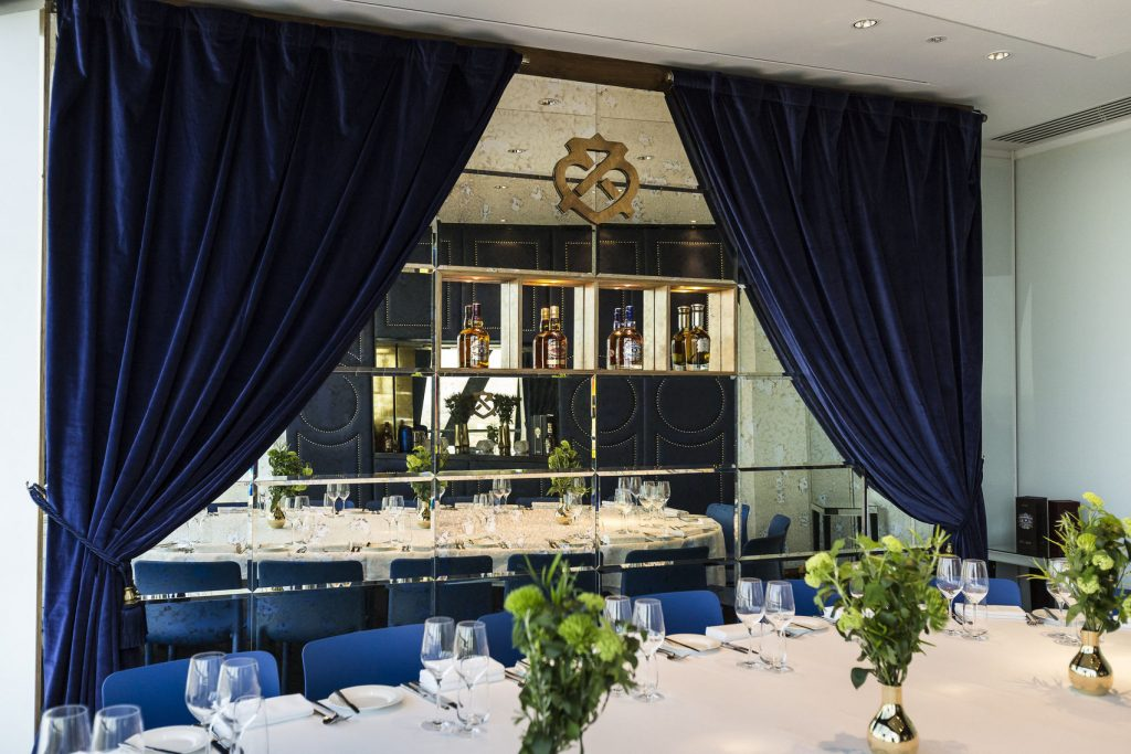 a large mirror on the wall is reflecting an elegant private dining table with glassware placed on the top along with green bouquets in glass vases. The mirror is surrounded by thick blue velvet curtains.